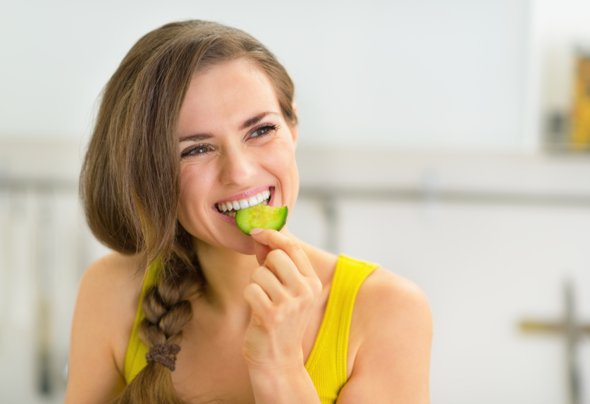 Portrait of young woman eating cucumber in kitchen