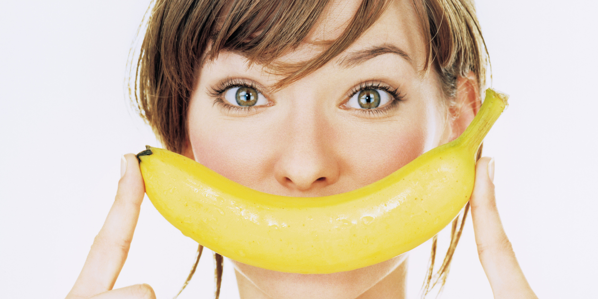 Young woman holding banana over mouth, portrait, close-up