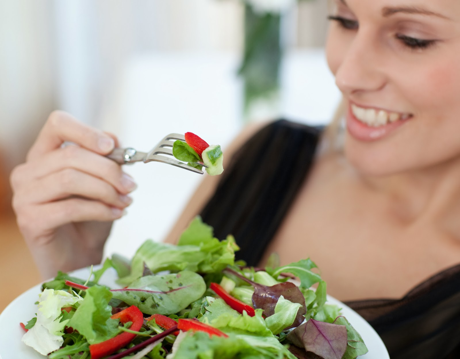 Close-up of a smiling woman eating a salad