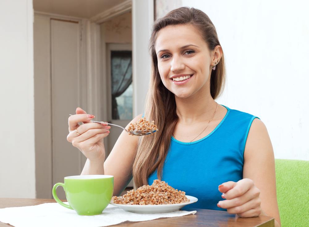 woman eats buckwheat with spoon at home interior