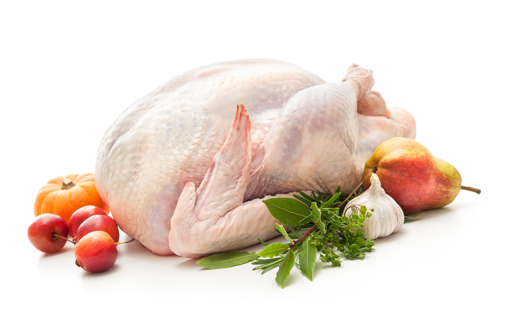 Uncooked turkey with herbs isolated on white background
