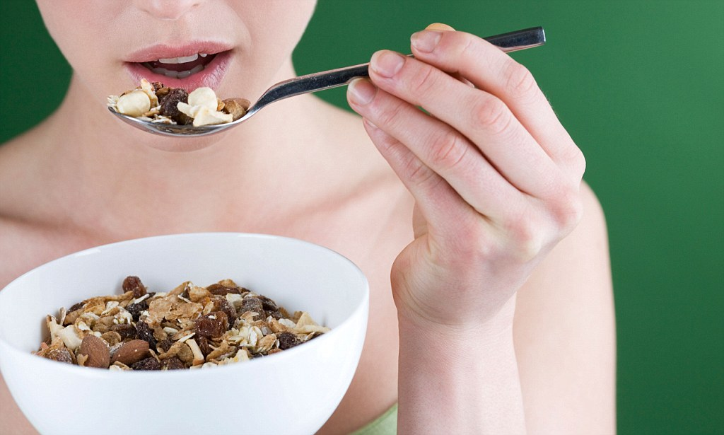 BCGNMM A woman eating muesli, close-up