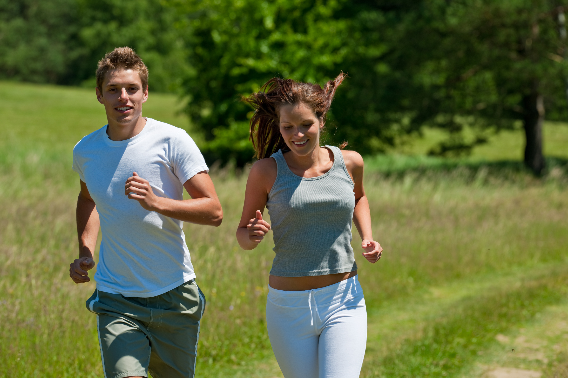 Young man and woman running outdoors, shallow DOF