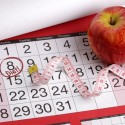 Dieting concept apple and tape measure on a calendar with a date to start a diet