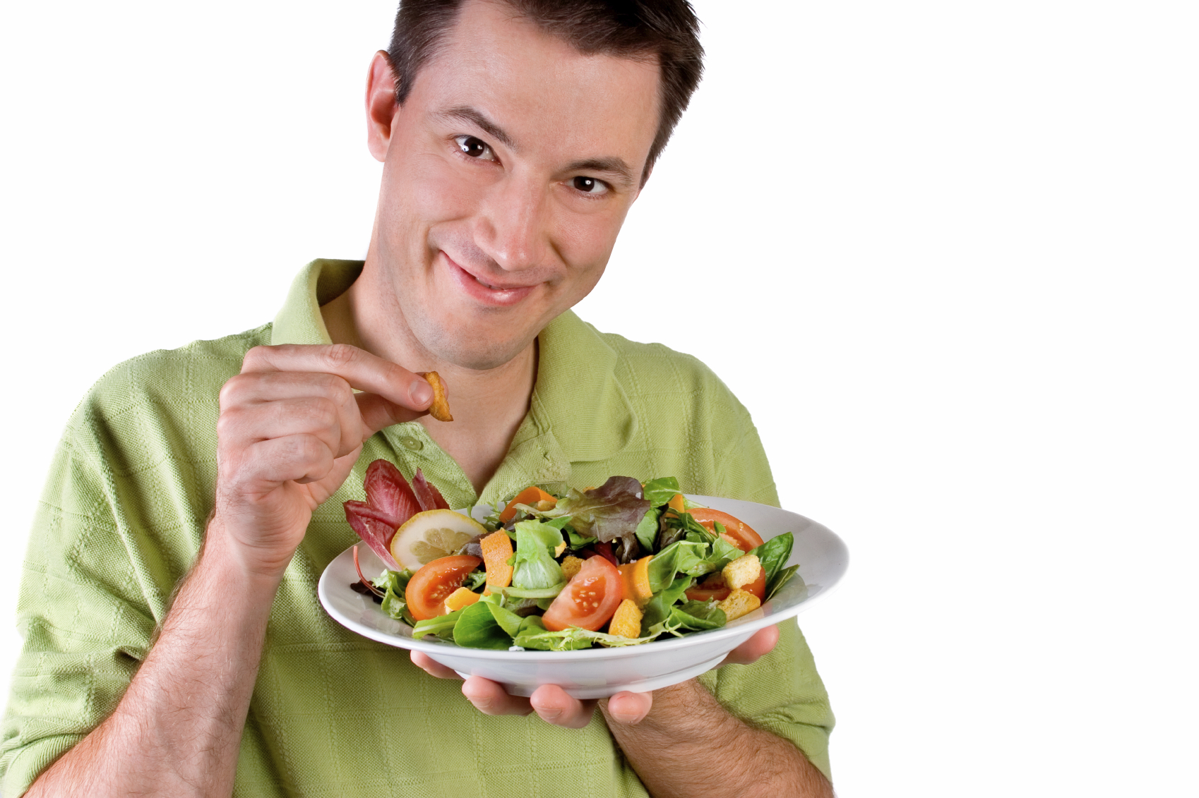 A smiling gentleman puts the finishing touch on his healthy salad.