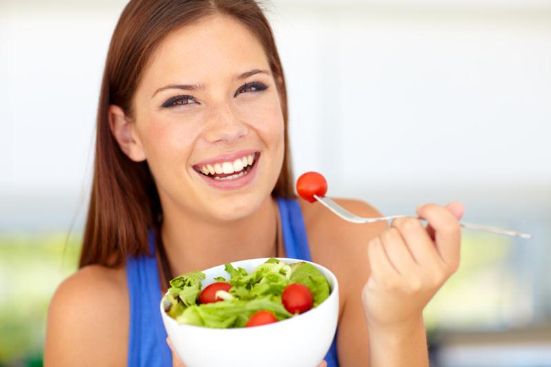 Beautiful young woman enjoying a healthy green salad